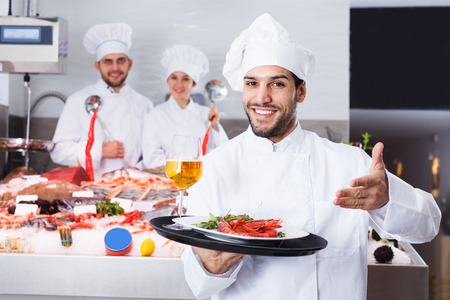 Portrait of confident smiling chef standing with serving tray in fish restaurant