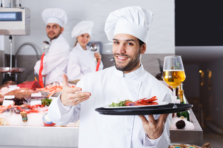 Handsome adult male chef with dishes on serving tray welcoming to fish restaurant