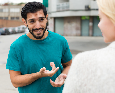 Man is acquaintancing with young woman on the street. Stock Photo