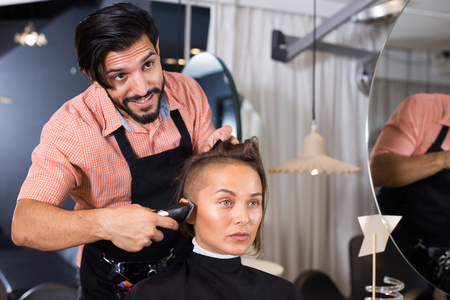 Positive sexy adult hairdresser working with hair clipper with woman  Standard-Bild