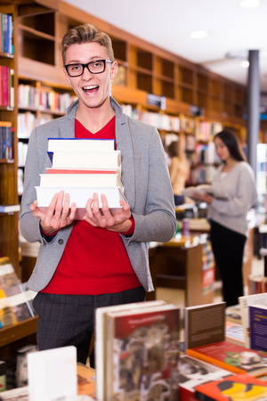 Portrait of guy standing in bookstore with pile of books in hands Stock Photo
