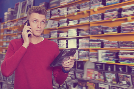 Smiling guy talking on mobile phone while choosing movies on DVD in shop