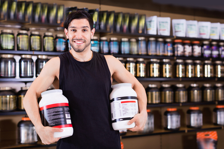 Young smiling cheerful positive bodybuilder showing power and holding pot  of sport nutrition products in shop