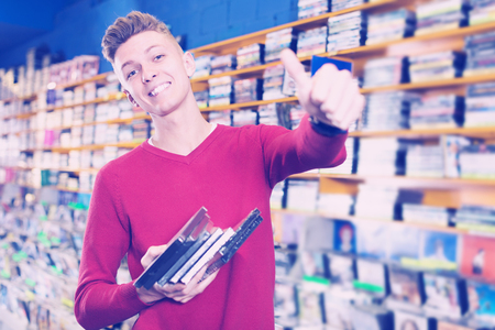 Smiling guy holding stack of DVDs bought in store giving thumbs up