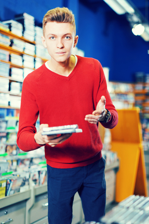Young man standing near shelves with CD and DVD in store, holding out CD case to somebody Stock Photo