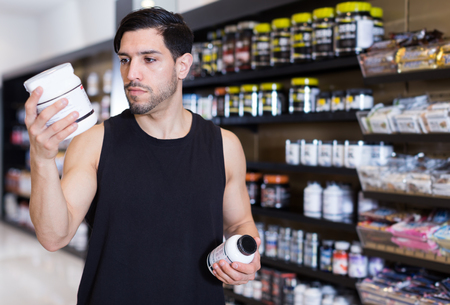 Serious muscular guy holding sport nutrition products in sport shop