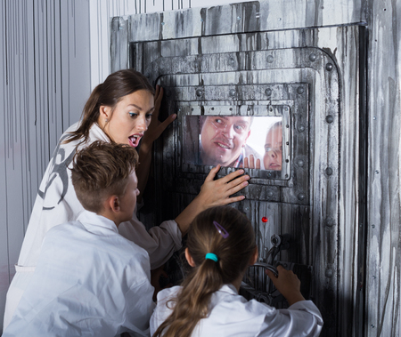 Mother with childred are helping dad and girl get out of the locked door in quest room.