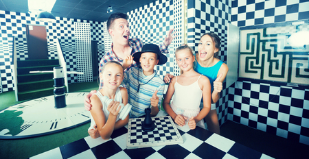Parents with their children are satisfied after visit of escape room stylized under chessboard.