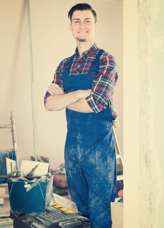 Portrait of smiling builder standing in repairable room Stock Photo