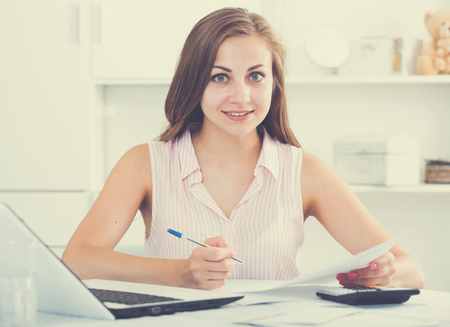 Attractive young woman using laptop and working on her finances at home