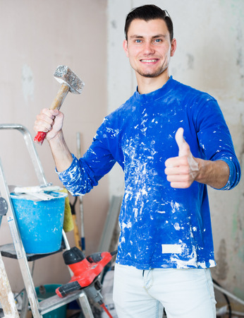 Smiling male builder showing thumb up with hammer in hand