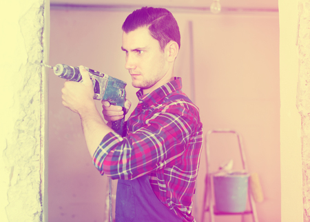 Professional worker standing with drill in hands in repairable room