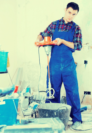 Male builder mixing plaster in bucket with electric mixer at room Stock Photo