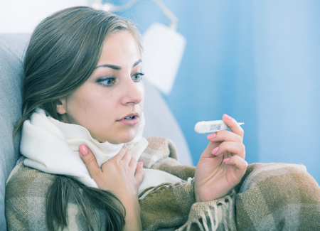 Sick young woman at home on sofa covering with plaid checking temperature Reklamní fotografie - 101012812