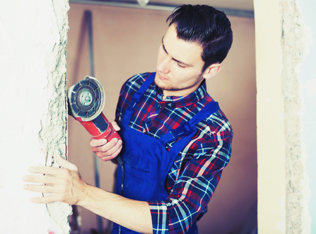 Professionality male contractor using professional angle grinder for cutting wall