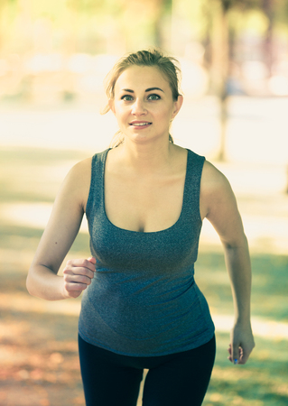 Young happy european female in sportwear running in the sunny park