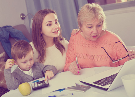Aged woman is mastering technology near laptop with her daughter and grandson at home. Standard-Bild