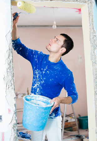 Male construction worker priming and painting doorway with painting roller