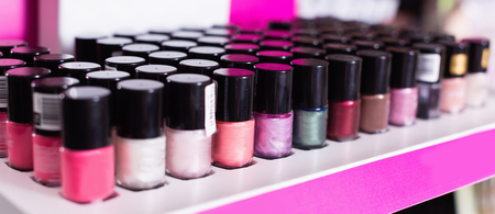 Variety of stylish, fashionable, diverse, colorful nail polishes on showcase in cosmetic boutique