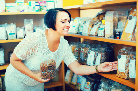 Smiling mature female customer holding with cereal products in healthy food store Reklamní fotografie