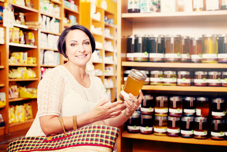 Portrait of positive mature woman choosing different kinds of natural honey in healthy food store