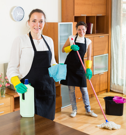 Happy professional adult cleaners washing apartment with rag and mop Stock Photo