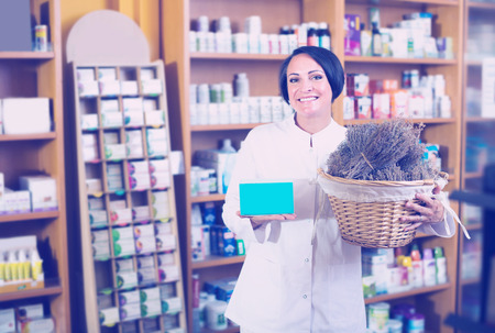 cheerful woman seller in uniform holding bunch of dried herbs in pharmaceutical store