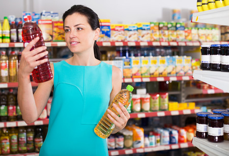 Woman choosing different oil in bottle at the supermarket