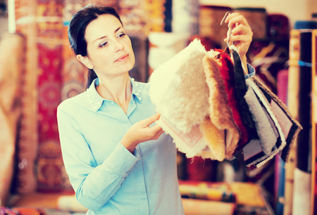 Adult woman shopping carpet and showing samples in interior store