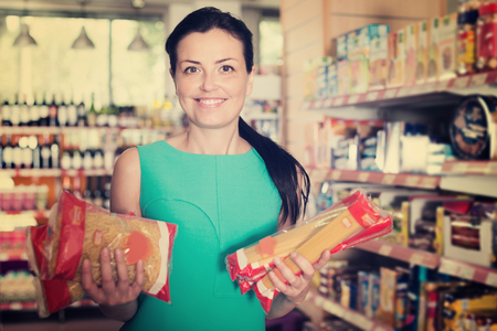 Smiling adult woman choosing pack of spaghetti and macaroni at the supermarket Stock Photo