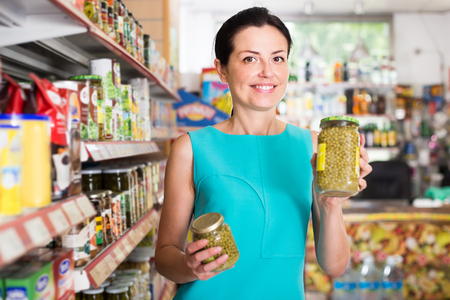 Portrait of beautiful female in the shop holding preserved jar of green peas Stock Photo
