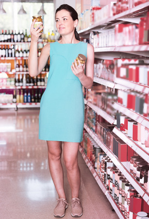 Smiling female is holding jar of preserved olives in the shop. Stock Photo