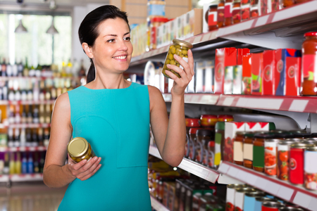 Girl is holding jar of preserved olives in the shop.  Stock Photo