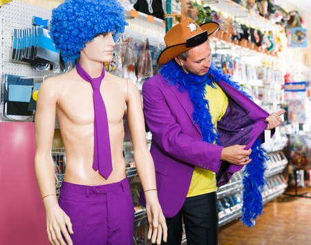 Laughing man is staying with comically dressed dummy in the shop.  Reklamní fotografie