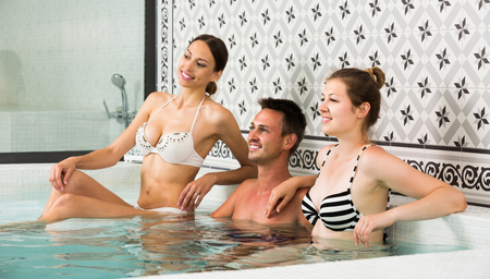 Young happy spanish people relaxing in hot tub in spa