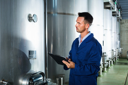 Young diligent man in coat taking notes in secondary fermenting section on wine factory 免版税图像 - 101051661