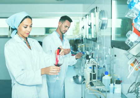 Two young efficient smiling  researchers in white coat checking wine acidity and sugar saturation in chemical laboratory Foto de archivo