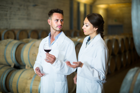 two young winery employees in white coats checking up quality of wine in aging section on winery manufactory 免版税图像