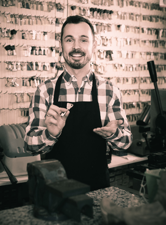 happy male worker showing key he made in repair workshop Archivio Fotografico