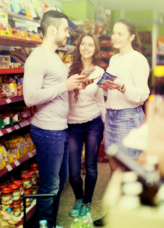 People have a discussion inside a supermarket near grocery shelf