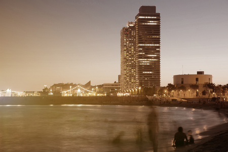 View of Barceloneta beach with Mapfre tower and Arts Hotel in Barcelona in sunset  Stock Photo