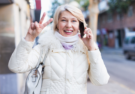 Smiling mature female is walking and talking by phone outdoor.