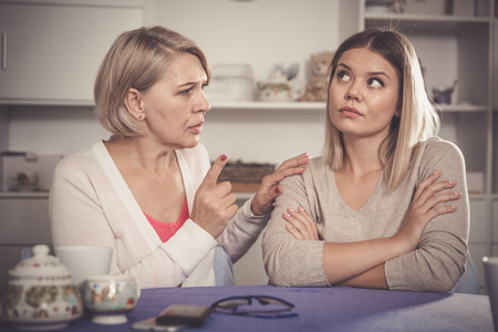 Dissatisfied elderly mother chastises saddened grown-up daughter Stock Photo