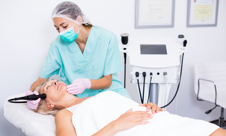 Qualified female cosmetologist during procedure cryolipolyse in modern aesthetic clinic Stock Photo
