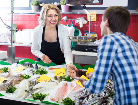 Mature woman selling fish to male customer in store Stock Photo