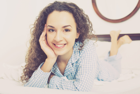 Portrait of curly haired woman lying in bed and smiling
