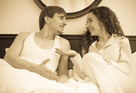 Portrait of happy young spouses having funny conversation in bed