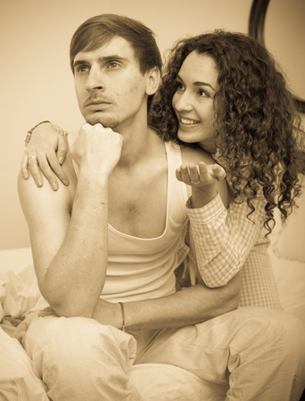 Misunderstood wife trying to reconcile with offended husband in bedroom Imagens