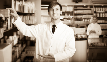 Smiling pharmacist and pharmacy technician posing in pharmacy