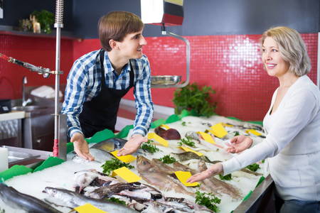 Adult female customer choosing and buying fish in shop